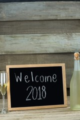 Champagne bottle and glass kept beside the slate with welcome