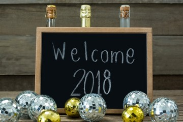 Welcome 2018 written on slate board with baubles and champagne