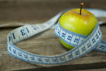 Green apple with measuring tape on wooden table
