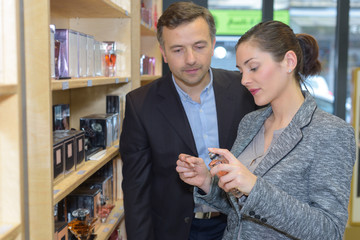 beautiful saleswoman showing beauty products to male customer