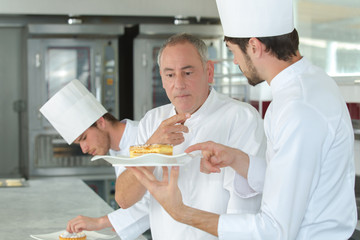 apprentices chefs at work with experienced master