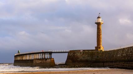 Whitby west pier and light from the beach at low tide