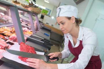 female butcher cutting a meat