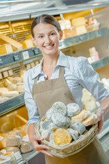 Woman holding a basket of different cheeses