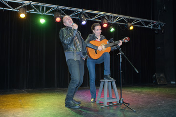 Couple singing and playing guitar on stage