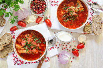 Two bowls of Ukrainian borscht on embroidered napkins, bread, sour cream, spices, onions, garlic, tomatoes and parsley on a white wooden background.