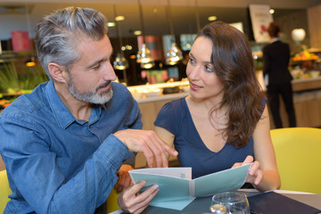 Middle aged couple choosing from menu