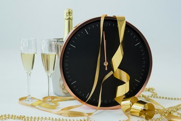 Champagne with clock and glass on white background