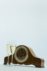 Champagne glass and clock on white background