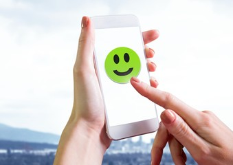Hand touching smiley face on phone