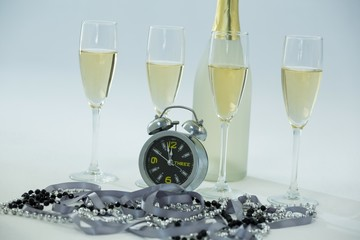 Champagne with alarm clock and glass on white background