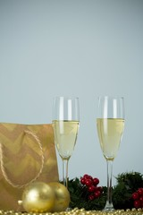 Champagne flute and christmas decoration against white