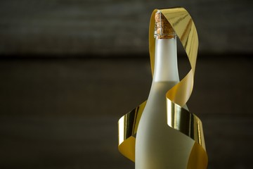 Champagne bottle with golden ribbon against wooden background