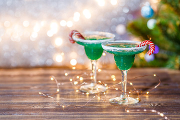 Christmas image of two wine glasses with green cocktail, caramel sticks