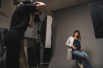 Pregnant woman doing a photoshoot with a female photographer in a studio