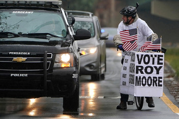 Police stop and speak to a man as he rides his bike with signs of support for Alabama Republican senatorial candidate Roy Moore around a venue that will host U.S. President Donald Trump later in the day in Pensacola, Florida