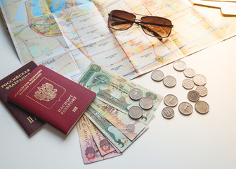 Arab dirhams and a Russian passport on the background of the card and sunglasses. The concept of travel.