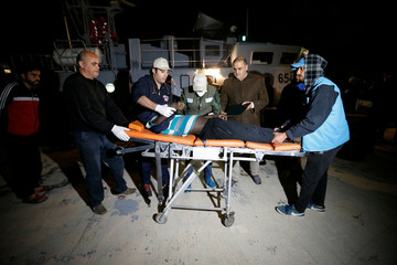 A migrant is carried on a stretcher as he arrives at a naval base after he was rescued by Libyan coast guards in Tripoli