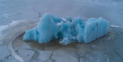Aerial photo of blue iceberg in frozen lagoon, Fjallsárlón Iceland