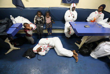 Migrants rest after they were rescued by Libyan coast guards at the coast of Tripoli in Libya