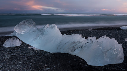 Glacial fragment of ice on black beach at sunset, Jokulsarlon Iceland