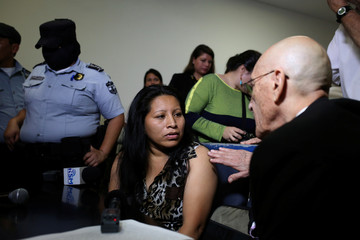 Teodora del Carmen Vasquez speaks with her attorney as she waits in a court of justice for a sentence review hearing in San Salvador