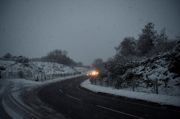 Approaching cars illuminate the road during heavy snowfall on the Mourne Mountains near the village of Hilltown