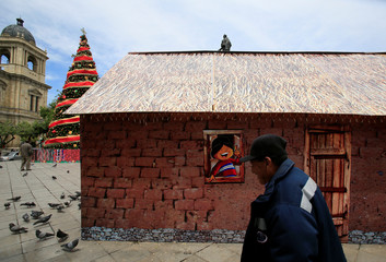 """A man walks in front of a replica of the house where Bolivia's President Evo Morales was born, as it is presented by the government as """"The House of Desires"""", during the Christmas season at the Murillo square in La Paz"""