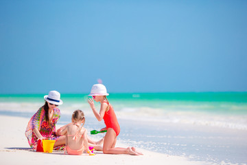Mother and little daughters making sand castle at tropical beach