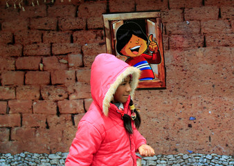 """A girl walks pass the facade of a replica of the house where Bolivia's President Evo Morales was born, as it is presented by the government as """"The House of Desires"""", during the Christmas season at the Murillo square in La Paz"""