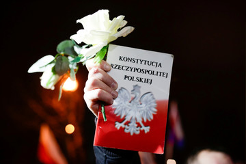 A demonstrator holds a Polish Constitution during a protest in Krakow