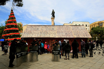"""Riot policemen stand next to a replica of the house where Bolivia's President Evo Morales was born, as it is presented by the government as """"The House of Desires"""", during the Christmas season at the Murillo square in La Paz"""