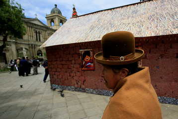 """A woman walks in front of a replica of the house where Bolivia's President Evo Morales was born, as it is presented by the government as """"The House of Desires"""", during the Christmas season at the Murillo square in La Paz"""