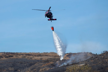 An U.S. military helicopter from Camp Pendleton makes a water drop on a hotspot caused by the Lilac Fire, a fast moving wild fire in Bonsall, California
