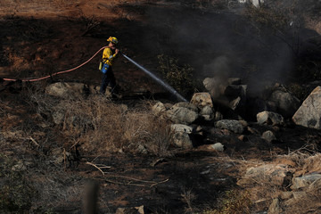 A firefighter puts water on a hotspot caused by the Lilac Fire, a fast moving wildfire in Bonsall, California