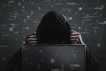Hacker in a black hoodie, laptop, binary code
