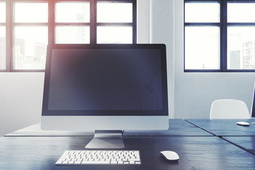 Blank computer screen on a black office table