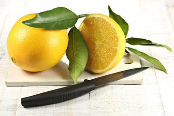Orangen mit Blättern auf altem Keramikbrettchen