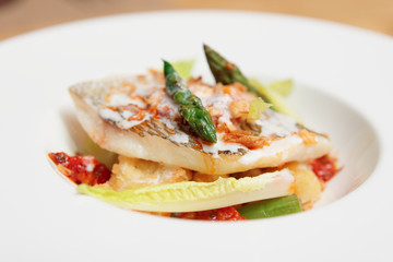 Grilled fish with asparagus in plate