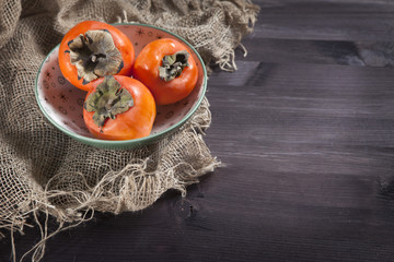 the persimmon in a plate on a napkin made of canvas on a dark wooden table