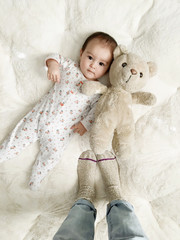 Portrait of baby with teddy bear and moms feet