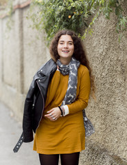 Young woman putting on leather jacket and smiling