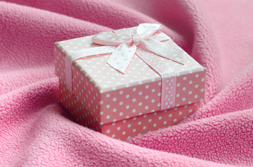 A small gift box in pink with a small bow lies on a blanket of soft and furry light pink fleece fabric with a lot of relief folds. Packing for a gift to your lovely girlfriend