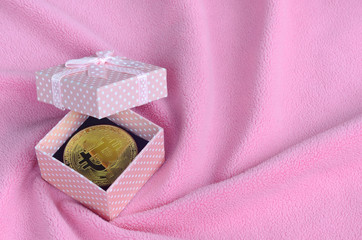 The golden bitcoin lies in a small pink gift box with a small bow on a blanket made of soft and fluffy light pink fleece fabric with a large number of relief folds