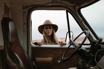 woman in hat looking in van window from outside