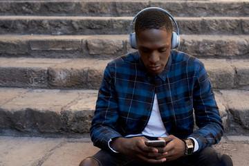 Young man listening to music via headphones.