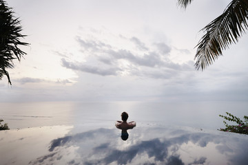 Young  man relaxing in an infinity pool in Bali