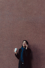 Young professional woman talking on the phone with a coffee outside her office building