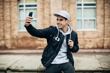 Cool young man taking a selfie outside.