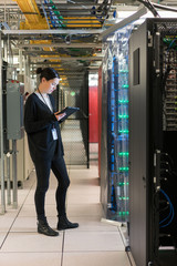 Young woman in a server room looks down at her digital tablet